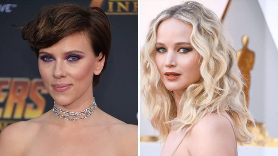 Die Schauspielerinnen Scarlett Johansson und Jennifer Lawrence stehen in schulterfreien Kleidern auf dem roten Teppich
