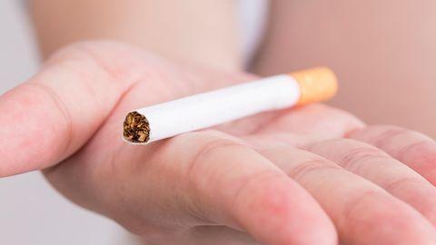 Auf einer Handfläche liegt eine Zigarette