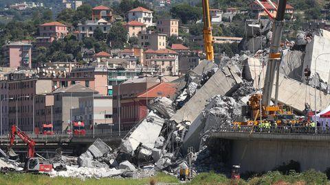 Italien, Genua: Mit Baggern und Kränen werden Trümmerteile einer teilweise eingestürzten Brücke weggeräumt.