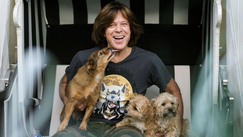 Schlagersänger Jürgen Drews sitzt mit seinen Hunden im Garten