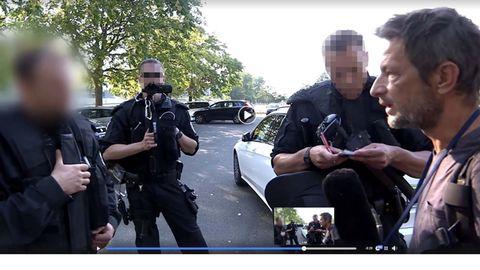 Der freie TV-Journalist Arndt Ginzel diskutiert während einer Pegida-Demo mit Polizisten