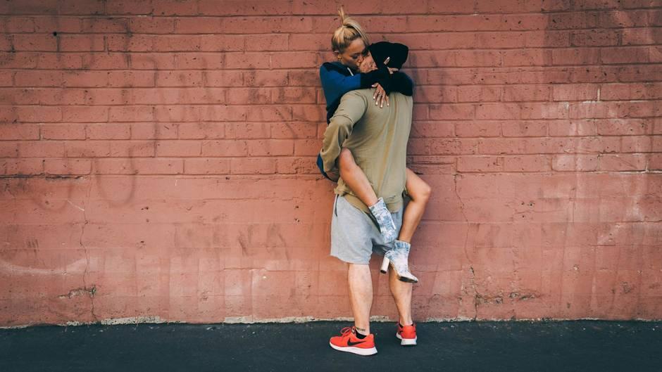Zwei Menschen küssen sich vor einer Mauer