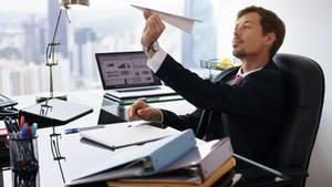 Mann imBüro hält einen Papierflieger in der Hand