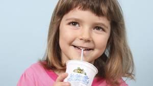Ein kleines Mädchen trinkt Schulmilch.