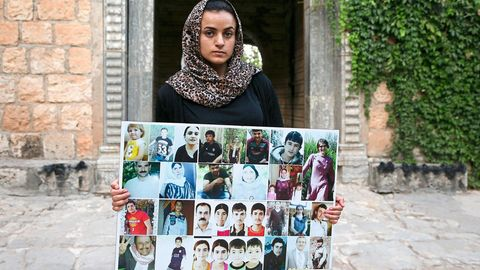 Aschwaq Taloo zeigt vor dem Lalisch-Schrein im Nordirak Bilder von Opfern aus ihrem Dorf