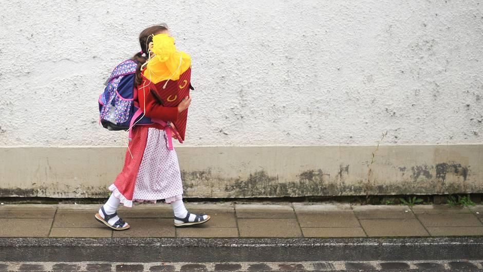 Ein Mädchen geht im Dirndl zu Einschulung