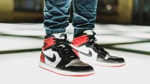 Ein Mann steht in Nike-Schuhen auf einer Glasscheibe, die von unten beleuchtet wird