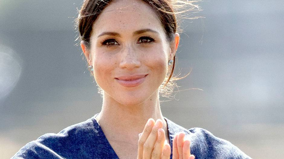 Im blauen Sommerkleid lächelt Herzogin Meghan von Sussex und klatscht in die Hände