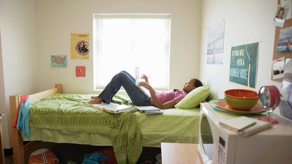 Ein Mädchen liegt auf dem Bett in einem Internat-Zimmer mit ihrem Laptop auf dem Schoß