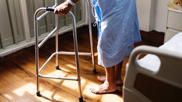 Eine Frau im steht im Operationskittel an einer Gehhilfe