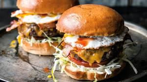 Ein Burger mit Kohl, Salat, Tomate, Fleisch, Bacon und Spiegelei