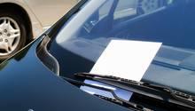 Hinter dem Scheibenwischer eines Autos klemmt eine Notiz