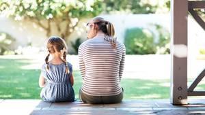 Mutter und Tochter sitzen auf Terasse