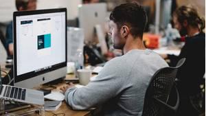 Ein junger Mann sitzt an einem Schreibtisch und arbeitet an einem großen Computer, neben ihm weitere Kollegen