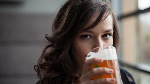 Eine junge Frau trinkt Bier