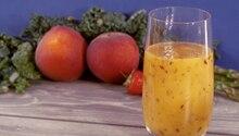 Ein Glas mit einem orangenen Smoothie darin steht vor zwei Pfirsichen, einer Erdbeere und etwas Grrünkohl