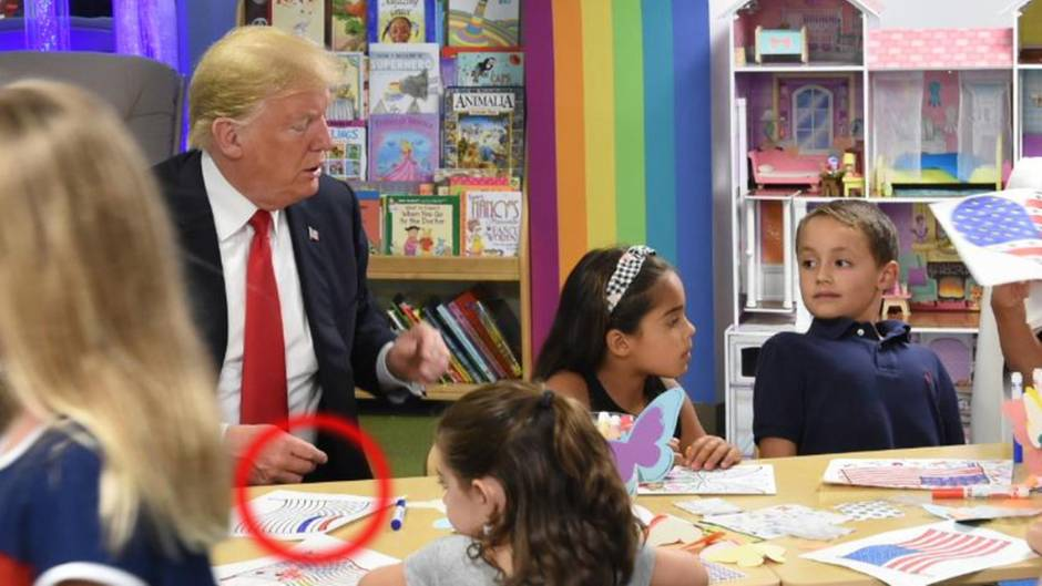 US President Donald Trump is sitting at the table with several children and sketching an American flag. & # 39; A stripe is blue