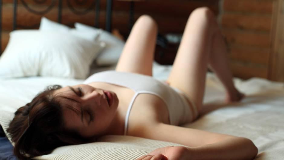 Eine junge Frau liegt in weißem Trägertop auf dem Rücken im Bett. Ihre nackten Beine hat sie angewinkelt