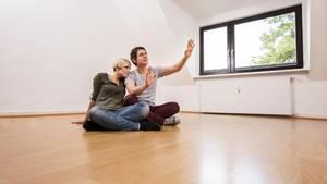 Ein Paar plant die Einrichtung einer neu bezogenen, leeren Wohnung