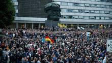 Demonstranten der rechten Szene stehen vor dem Karl-Marx-Denkmal in Chemnitz