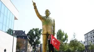 Mann posiert mit türkischer Flagge vor Erdogan-Statue in Wiesbaden