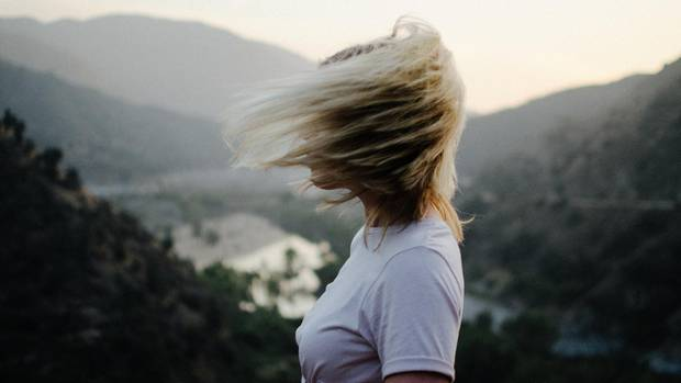 Eine junge Frau steht auf einer Anhöhe. Die Haare wehen ihr ins Gesicht.