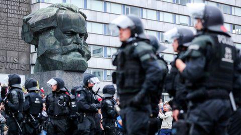 Polizei steht nach den rechten Krawallen unter der Karl-Marx-Büste in Chemnitz