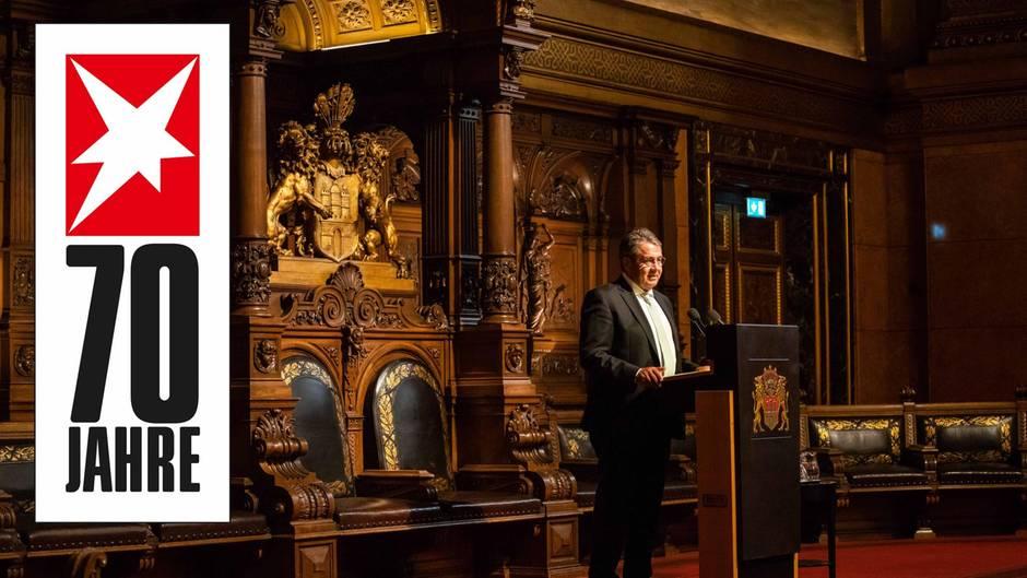 In einem Festsaal im Hamburger Rathaus steht SPD-Politiker Sigmar Gabriel vor einem geschnitzten Hamburger Wappen und spricht