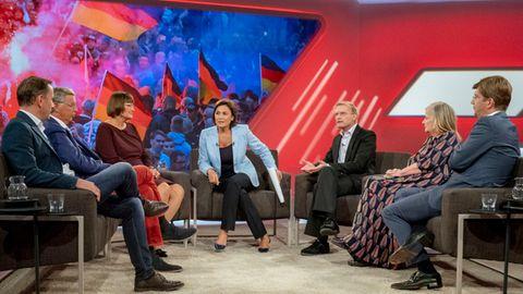 In einem TV-Studio sitzt Sandra Maischberger in der Mitte, links von ihr zwei Männer und eine Frau, rechts ebenfalls