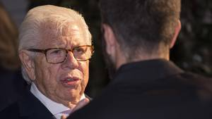 Carl Bernstein, ein älterer Man mit weißem Seitenscheitel und rechteckiger Hornbrille, unterhält sich mit einem Mann