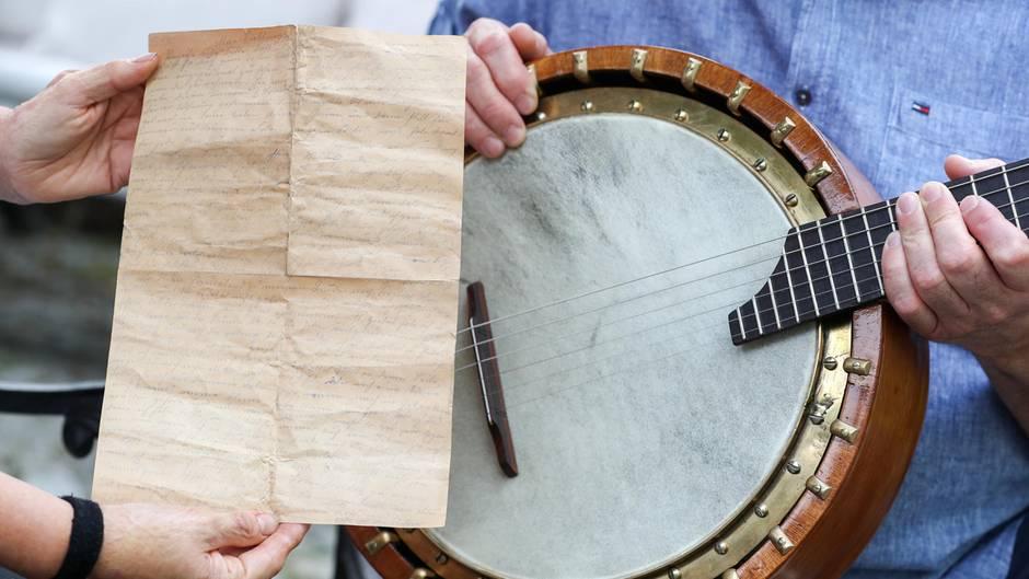 Zwei Hände halten einen vergilbten, oft gefalteten Liebesbrief vor ein altes Banjo, das ein Mann in blauem Hemd hält