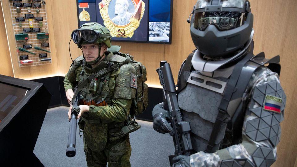Ein bestehender Anzug mit Exoskelett neben dem martialischen Prototypen auf dem Stand vonZNiiTochMash.
