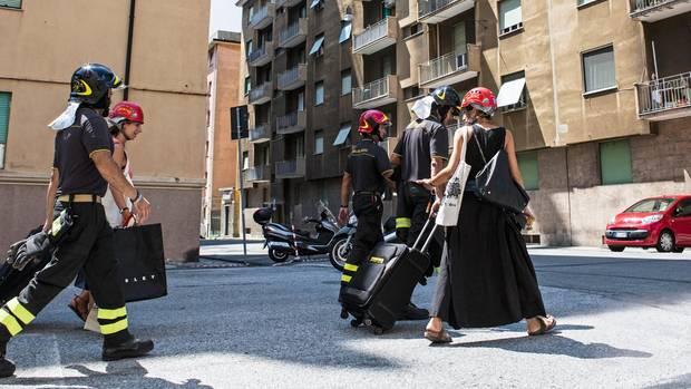 Die Feuerwehr begleitet zwei Genueserinnen zu ihren Wohnungen. Die Evakuierungen werden immer wieder unterbrochen – aus Angst vor einem weiteren Einsturz