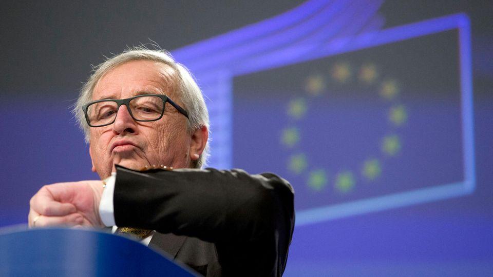Jean-Claude Juncker schaut im vor einer projezierten EU-Flagge auf die Uhr an seinem linken Handgelenk