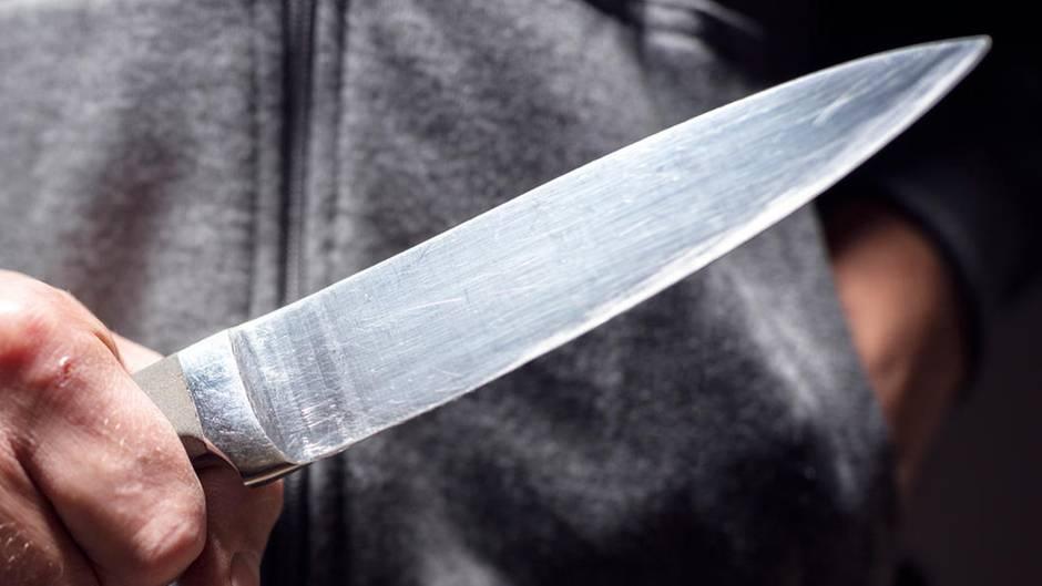 Ein Mann hält ein Messer in der Hand