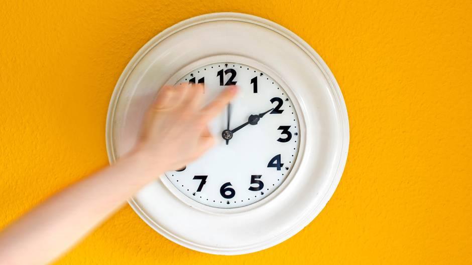 Eine Frau stellt an einer Wanduhr die Zeit um