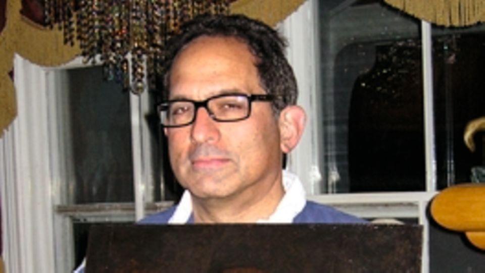 Robert Simon zeigt das Werk mit dem freigelegten Pentimento