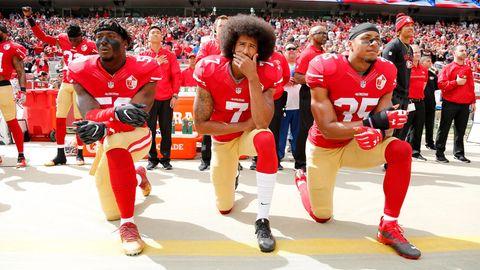 Die Geste, die ihn (und andere Sportler) berühmt gemacht hat:Colin Kaepernick (M.), Eli Harold (l.), und Eric Reid während der Nationalhymne vor dem Spiel der San Francisco 49ers gegen dieDallas Cowboys