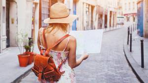 Frau mit Strohhut steht in einer schmalen Gasse und schaut auf eine Landkarte
