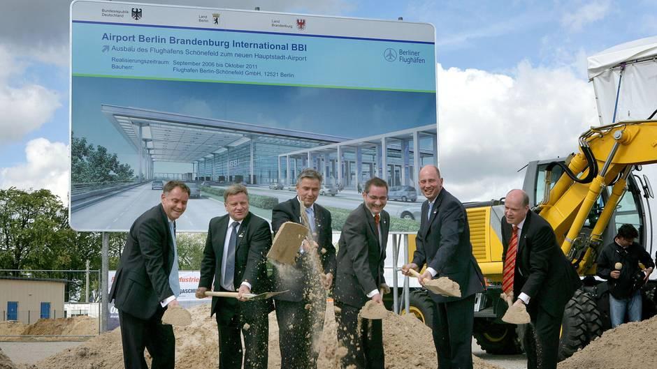 Symbolischer Spatenstich  Am 5. September 2006 begann der Bau des neuen Hauptstadtflughafens, damals noch Airport Berlin Brandenburg International (BBI) genannt. Die Herren stehen vor einem Schild, das die Eröffnung für den Oktober 2011 vorsieht.