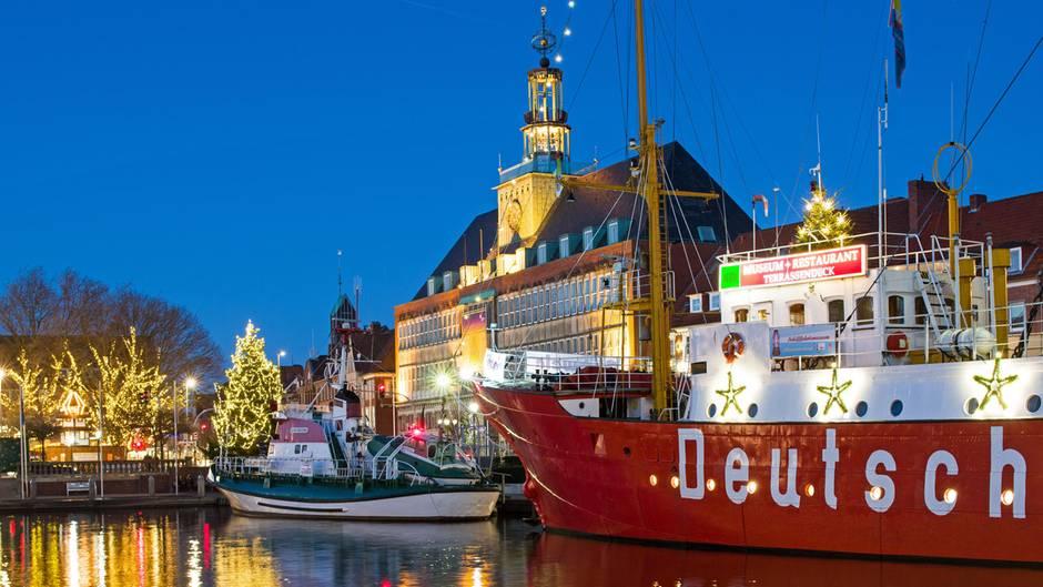 """Das Museumsfeuerschiff """"Amrumbank"""" im Hafenbecken von Emden, dahinter der Seenotkreuzer der Deutschen Gesellschaft zur Rettung Schiffbrüchiger und das Rathaus der 50.000-Einwohner-Stadt."""