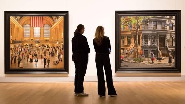 """Kunsthalle Emden:In der Ausstellung """"The American Dream"""" stehen zwei Besuchervor den Gemälden """"Grand Central Terminal""""und """"A Bend in the Road""""des Malers Stone Roberts."""