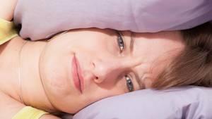 Eine Frau liegt mit gerunzelter Stirn zwischen zwei Kissen