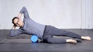 Der gesunde und fitte Rumpf: Side Over Prep  Ausgangsposition: den mittleren Brustkorb seitlich über die Rolle legen, Hände hinter dem Kopf, Finger verschränkt, Ellenbogen seitlich, unteres Bein 90 Grad gebeugt, oberes Bein seitlich in Linie mit Hüftgelenk ausgestreckt und parallel Bewegungsablauf: beim Einatmen Rumpf absenken, beim Ausatmen Rumpf seitlich in Diagonale heben  Übung im Detail:Mit dem Einatmen senkst du den Oberkörper seitlich über die Rolle ab. Mit dem Ausatmen hebst du den Oberkörper in eine Diagonale an. Dabei wird die Bewegung aus deiner Taille initiiert. Der Nacken bleibt lang. Außerdem bleibt das Becken stabil, genauso wie das ausgestreckte Bein. Am Schluss kommt die Belohnung: Bleib unten, und zieh mit der unteren Hand an dem oberen lang ausgestreckten Arm, und atme ein paar Züge tief ein und aus. Was für eine Wohltat! 5-12 Wiederholungen.