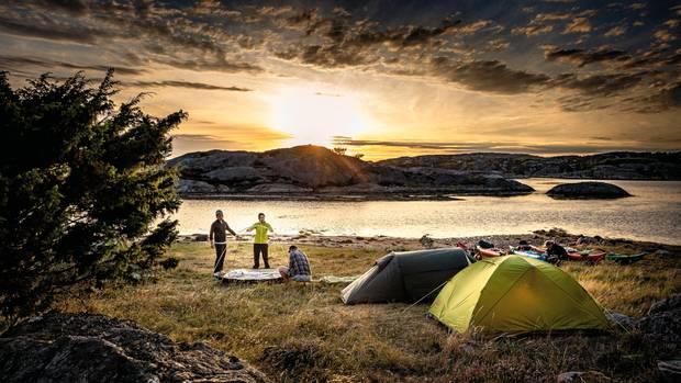 Während die Sonne untergeht, bauen die Kajakfahrer ihre Zelte für die Nacht auf.