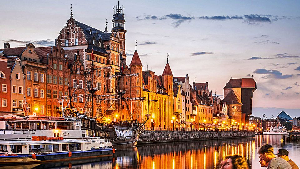 Danzigs Skyline am Abend: Gemeinschaftlich genießen Jugendliche an der Motława den Blick auf die glänzende Uferstraße.