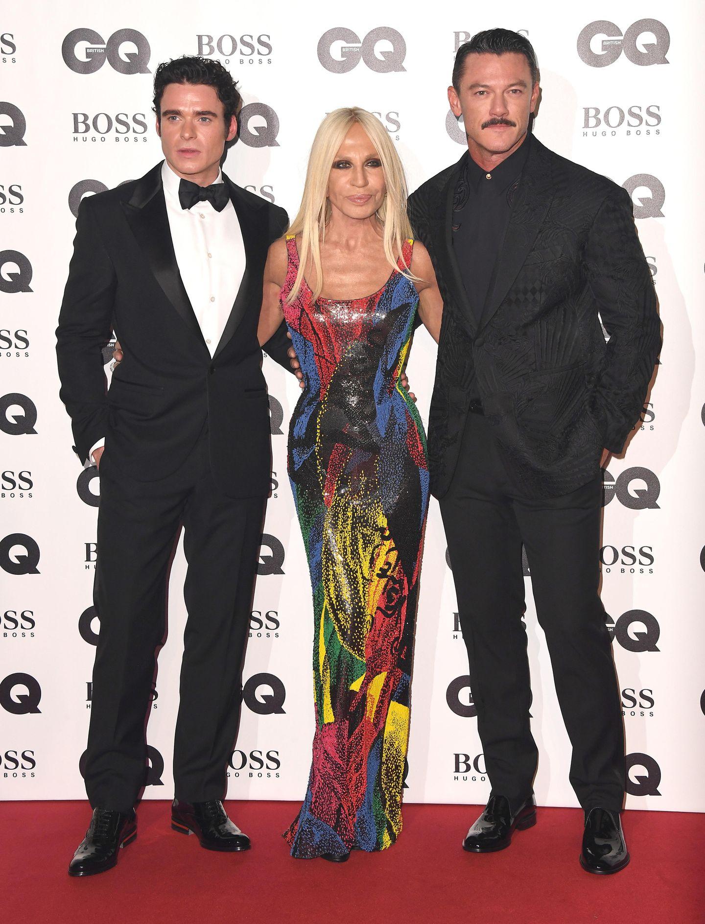 Designerin DonatellaVersace schmückte sich mit den SchauspielernRichard Madden (l.) undLuke Evans. Ihr buntes Kleid war selbstverständlich eine Eigenkreation.