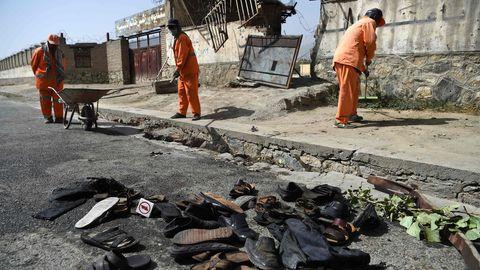 Nach einem Anschlag in Afghanistans Hauptstadt Kabul räumen Männer die Straßen auf