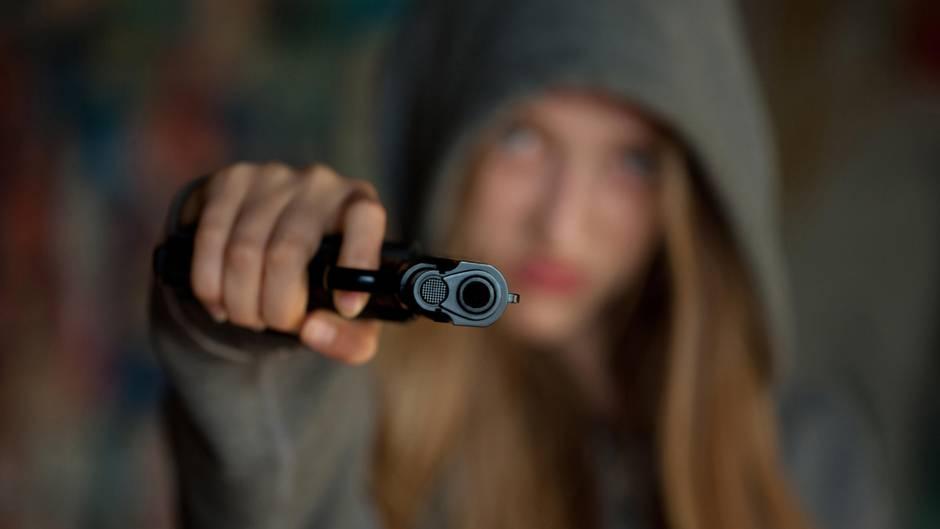 Ein Mädchen mit Kapuze hält eine Waffe in die Kamera