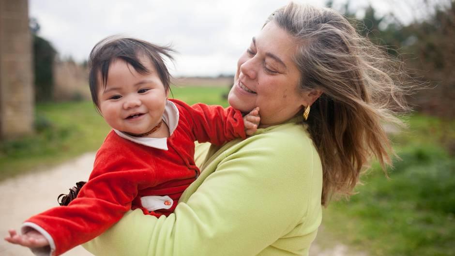 Eine Mutter hat ihre kleine Tochter im Arm